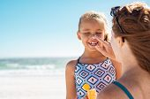 Young mother applying protective sunscreen on daughter nose at beach. Woman hand putting sun lotion  poster