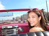 Car woman smiling happy on passenger seat in pink vintage convertible car. Young mixed race Asian /