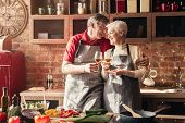 Cheers, Dear. Cheerful Senior Man And Woman Clinking With Wine Glasses In Kitchen Interior poster
