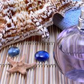 stock photo of sea salt  - Massage oil sea shell blue towel on a bamboo background - JPG