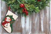 foto of muffs  - Christmas garland with a snowman stocking on a rustic wooden background - JPG