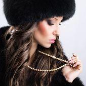 Beautiful woman wearing luxury fur coat and hat