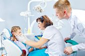 Dentist, medical assistant and a kid in dental office
