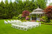 stock photo of gazebo  - A gazebo and white chairs at a wedding venue for the ceremony and reception - JPG