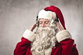 Santa Claus listening to the music with a pair of headphones