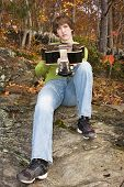 Young man with a guitar in the autumn woods