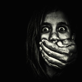 image of horrifying  - Horror portrait of a very frightened girl with an adult hand covering her mouth isolated on a white background - JPG