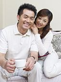 foto of snuggle  - portrait of a young asian couple sitting on family couch - JPG