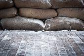 stock photo of sandbag  - Old brown sandbags on snow covered wooden floor taken on a winter morning - JPG