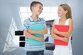 Smiling brother and sister holding their exercise books against room with holographic cloud