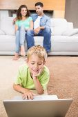 Cute little boy using laptop on the rug with parents sitting sofa at home in living room
