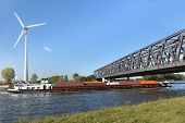 Container barge sailing under the Noordland bridge on the Scheldt-Rhine canal which connects the 2 g