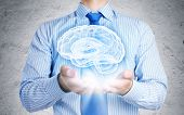 Close up of businessman holding image of brain in hands