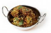Homemade onion bhajis, an Indian appetiser, served in a kadai or karahi wok.