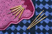 stock photo of knitwear  - Wooden hooks for knitting lie on the surface of pink and blue knitwear - JPG