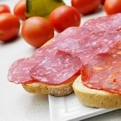 some slices of bread with salchichon and chorizo, spanish cured cold cuts