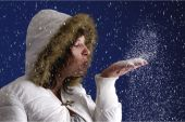 Young Woman Blowing Snow Wishes