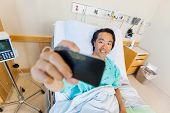 Mature male patient taking self portrait through cell phone in hospital