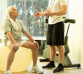 Personal trainer explains to a senior man how to do exercise on a fitness ball