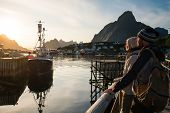 stock photo of reining  - Young travellers couple looking at sunset in Reine village - JPG