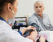 Senior man measuring blood pressure at doctor's office