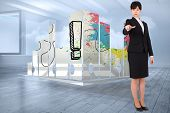 Focused businesswoman pointing against room with holographic cloud