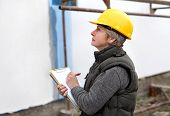 image of insulator  - Construction inspector examine styrofoam insulation of house facade wall - JPG