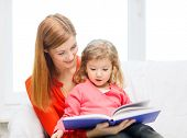 family, children, pre-school and happy people concept - happy mother and daughter with book