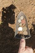 hand shovel with coins found metal detecting
