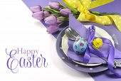 stock photo of yellow  - Happy Easter yellow and purple mauve lilac theme easter table place setting with sample greeting or copy space for your text here - JPG