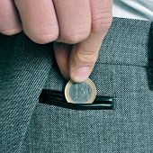 a man wearing a suit putting a one euro coin in the coin pocket of his trousers