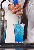 Barman preparing blue cocktail drink.