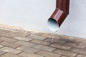 picture of downspouts  - Downspout with flowing rain water against grey wall - JPG