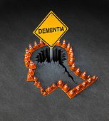 stock photo of neurology  - Dementia handicap concept as a group of three dimensional traffic cones shaped as a human head with a warning road sign emerging out of a hole in the street in the shape of a brain as a symbol of neurological problems - JPG