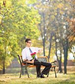 Young man holding flowers and checking the time seated on bench in park shot with tilt and shift len