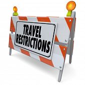 Travel Restrictions words on a road construction barrier, barricade or sign warning and blocking you
