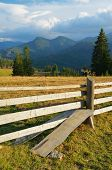 Summer landscape in the mountain village. Wooden fence with a stile