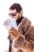 foto of hustler  - a young man wearing a sheepskin coat isolated over a white background holding banknotes - JPG