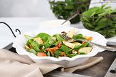 Green salad with apples, walnuts and cheese on plate, on light background