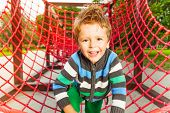 Cute smiling kid on red grid of playground