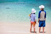 stock photo of coast guard  - Little kids in rash guards for sun protection on tropical beach during summer vacation - JPG