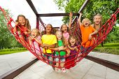 Group of kids sitting on playground net ropes