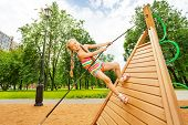 Girl with braids climbs on wooden construction