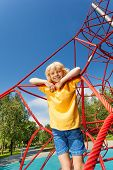 Boy stands on red ropes of net in the park