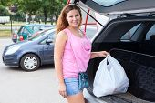 Smiling Woman Holding White Bag Full Of Groceries In Back Of Her Car