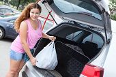 Attractive Young Woman In Pink Clothes Loading Bag In Suv
