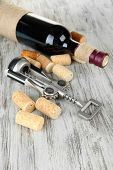 Corkscrew with wine corks and bottle of wine on wooden table close-up