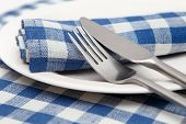 Linen napkins in blue checked with a knife, fork and plate closeup