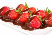 Strawberry dipped in chocolate fondue isolated on white