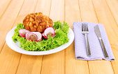Chicken Kiev on croutons with lettuce salad, on wooden background